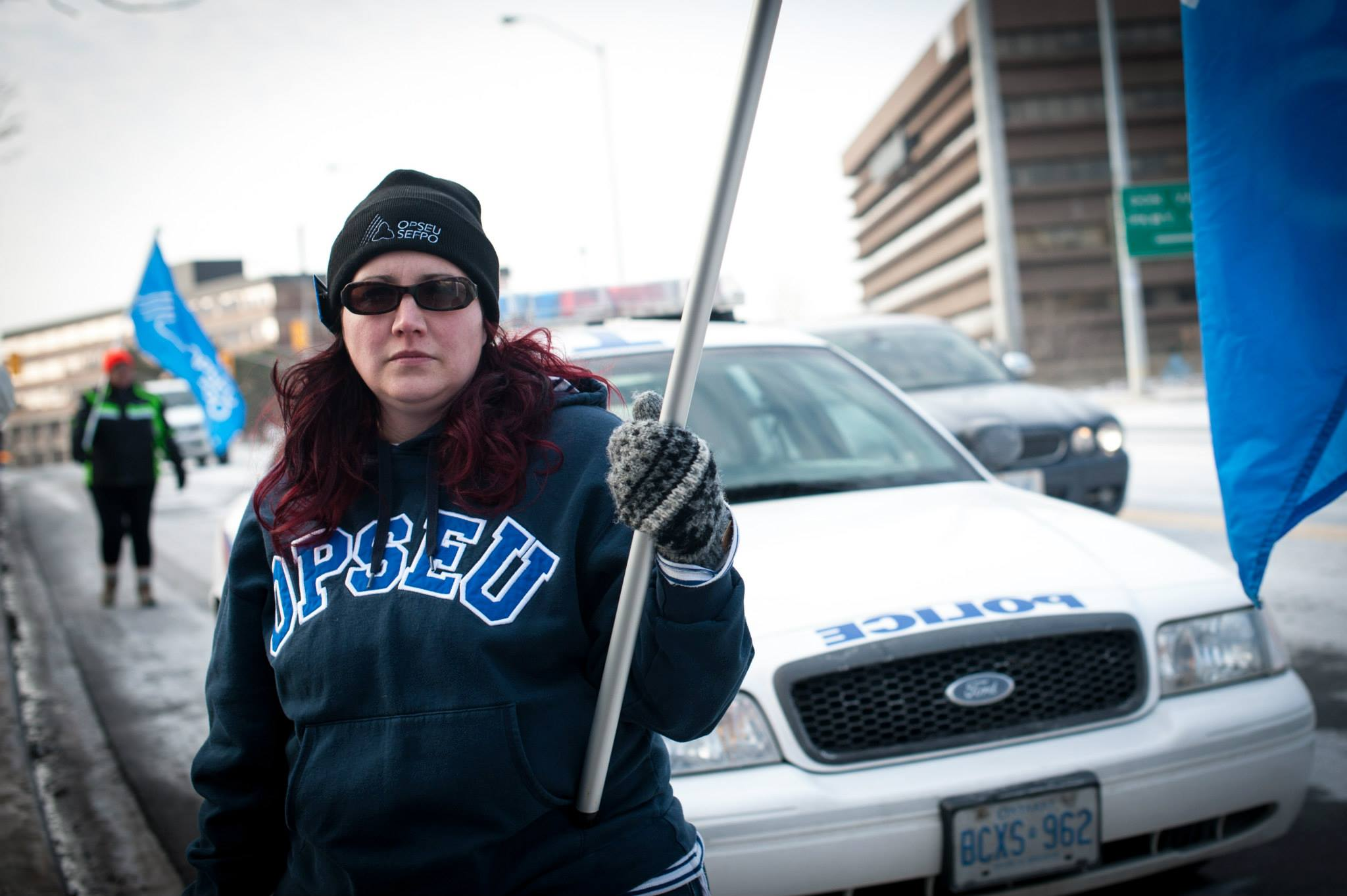 OPSEU member standing with OPSEU flag in front of police car